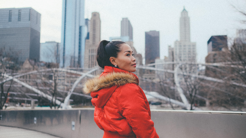 woman wearing winter coat standing outside on bridge